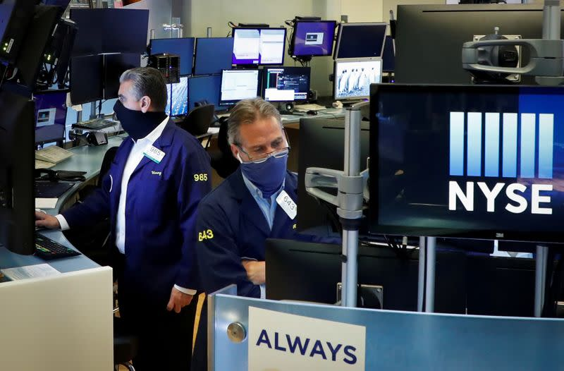 FILE PHOTO: Traders wearing masks work, on the first day of in person trading since the closure during the outbreak of the coronavirus disease (COVID-19) on the floor at the NYSE in New York
