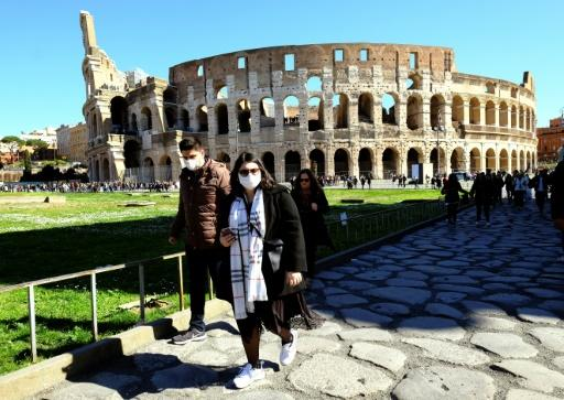 Tourists wearing protective masks visit the Colosseum in Rome as the coronavirus looks set to push the badly hit  economy into recession