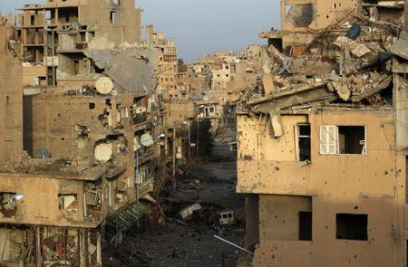 FILE PHOTO: A view shows damaged buildings in Deir al-Zor