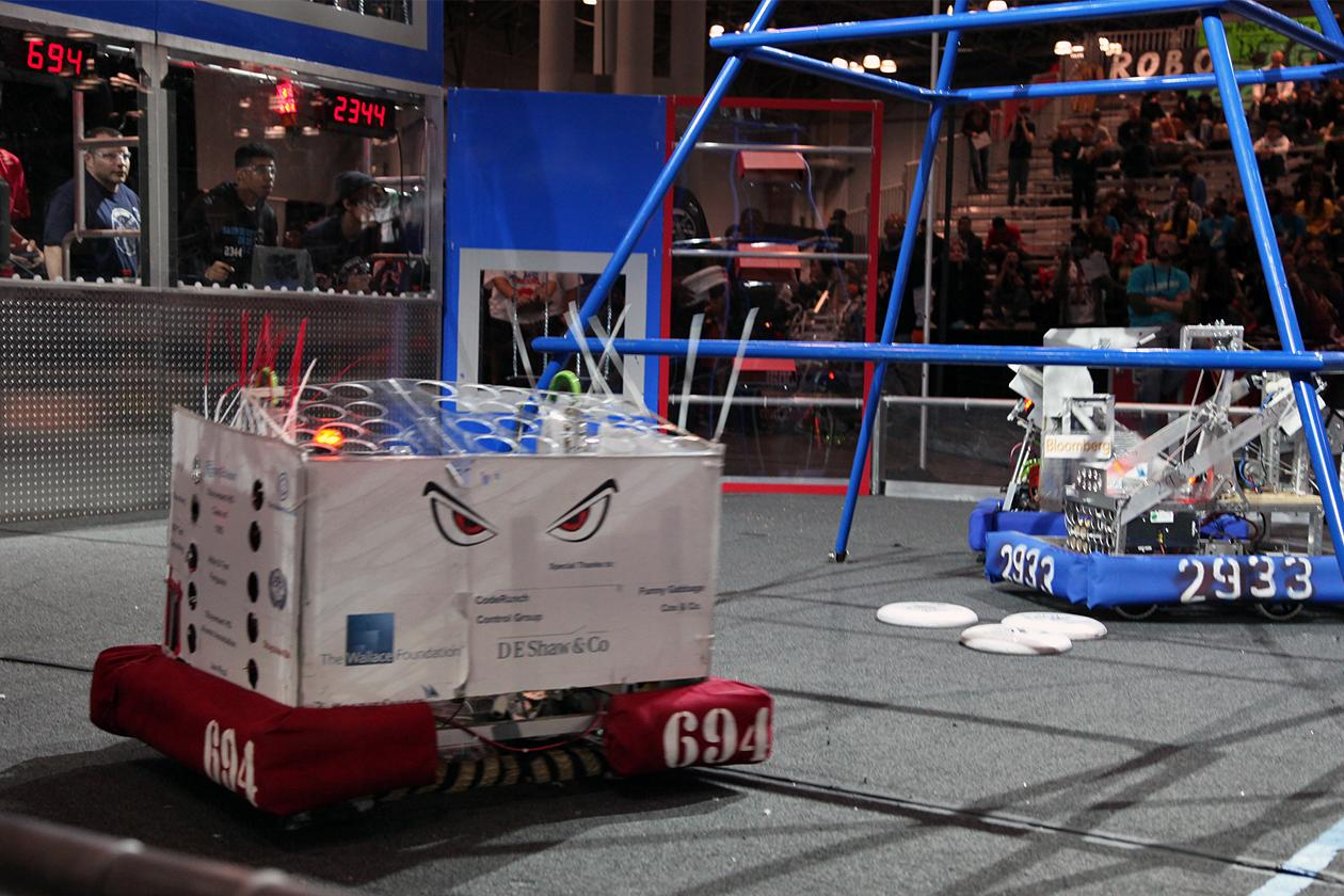 Two opposing robots rushing to retrieve discs on the field after the autonomous period.