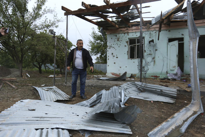 A man stands in a yard of a destroyed house damaged by shelling during fighting over the breakaway region of Nagorno-Karabakh in Agdam, Azerbaijan, Thursday, Oct. 1, 2020. Clashes broke out Sunday in Nagorno-Karabakh, a region within Azerbaijan that has been controlled by ethnic Armenian forces backed by the Armenian government since the end of a separatist war a quarter-century ago. Fighting has continued unchecked since then, killing dozens and leaving scores wounded. Armenian and Azerbaijani forces blame each other for continuing attacks. (AP Photo/Aziz Karimov)