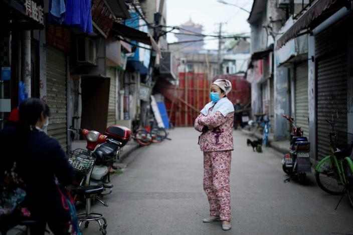 A resident wearing a face mask is seen at an old residential community blocked by barriers in Wuhan