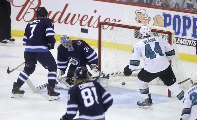 San Jose Sharks' Marc-Edouard Vlasic (44) scores on Winnipeg Jets goaltender Connor Hellebuyck (37) during the first period of an NHL hockey game in Winnipeg, Manitoba, Tuesday, March 12, 2019. (Trevor Hagan/The Canadian Press via AP)