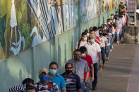 Voters line up at a polling station during a presidential runoff election in Guayaquil, Ecuador, Sunday, April 11, 2021. (AP Photo/Angel Dejesus)