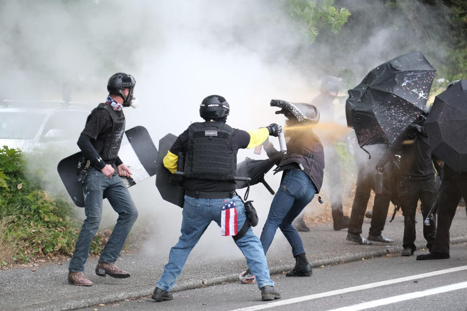 This Sunday, Aug. 22, 2021 photo, members of the far-right group Proud Boys and anti-fascist protesters spray bear mace at each other during clashes between the politically opposed groups in Portland, Ore. Police in Portland have been criticized that they did little to prevent violent clashes between right- and left-wing protesters on Sunday. (AP Photo/Alex Milan Tracy)