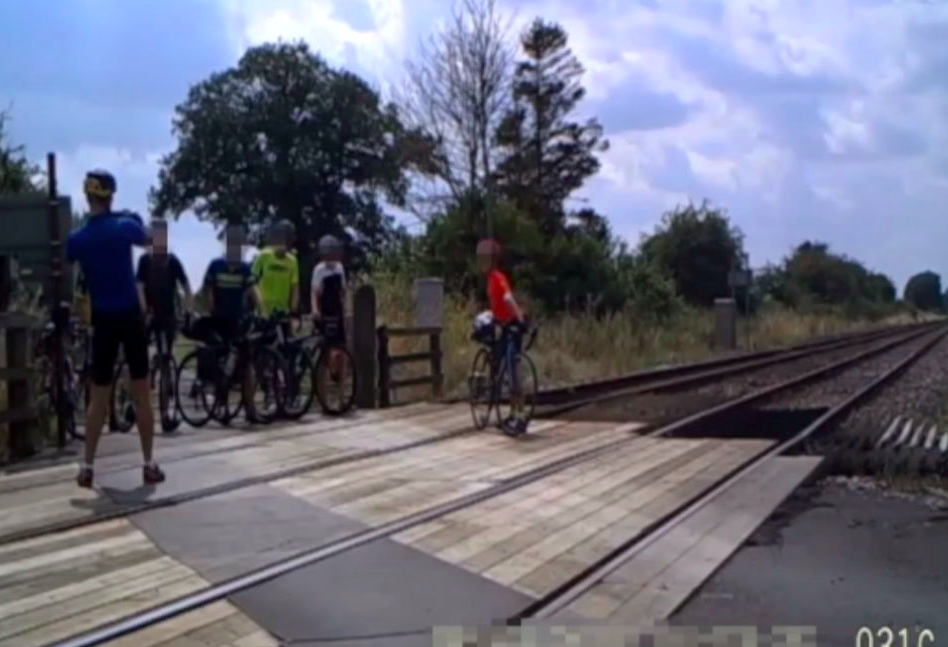 Another moment shows a group of cyclists who dismount their bikes and line up for a group photo on the crossing. (SWNS)