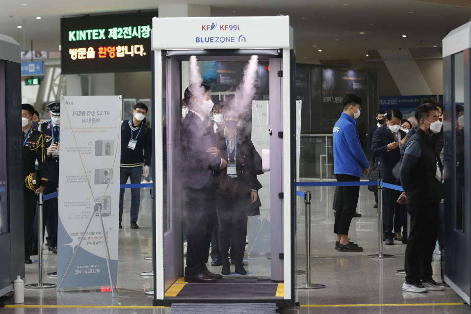 An attendee stands in a sterilizer as a precaution against the coronavirus as he arrives for a defense expo, DX Korea 2020, in Goyang, South Korea, Wednesday, Nov. 18, 2020. South Korea has recorded its largest daily increase in coronavirus infections in nearly three months as it gets set to tighten social distancing rules in the greater Seoul area. (AP Photo/Ahn Young-joon)