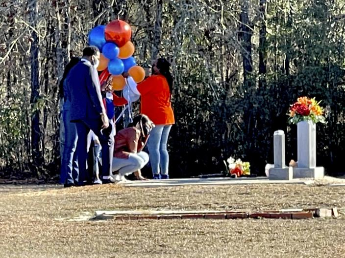 Wanda Cooper-Jones kneels before the grave of her son, Ahmaud Arbery, at the New Springfield Baptist Church in Waynesboro, Ga., on Tuesday, Feb. 23, 2021, to mark the one year anniversary of Ahmaud Arbery's death in Brunswick, Ga. Please use the following info for a second sentence in the cutline. Georgia lawmakers voted Wednesday, March 31, 2021 to repeal Georgia's citizen's arrest law after the law was raised as a defense for the men accused of shooting Ahmaud Arbery near Brunswick, Georgia in February 2020. (AP Photo/Lewis M. Levine, file)
