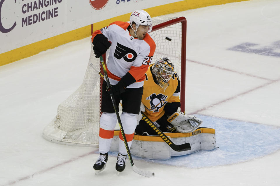 A shot by Philadelphia Flyers' Sean Couturier gets by Pittsburgh Penguins goaltender Tristan Jarry (35) for a goal as James van Riemsdyk (25) crowds the crease during the first period of an NHL hockey game Thursday, March 4, 2021, in Pittsburgh. (AP Photo/Keith Srakocic)