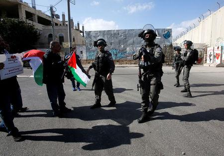 A demonstrator holds a Palestinian flag next to Israeli border policemen during clashes in the West Bank city of Bethlehem January 12, 2018. REUTERS/Mussa Qawasma