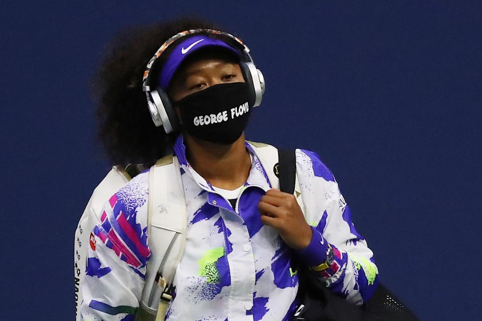 Naomi Osaka walks in wearing a mask with the name of George Floyd on it before her Women's Singles quarter-finals match.