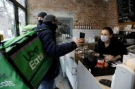 Courier from Uber Eats checks order as he picks up doughnuts during Fat Thursday in Warsaw