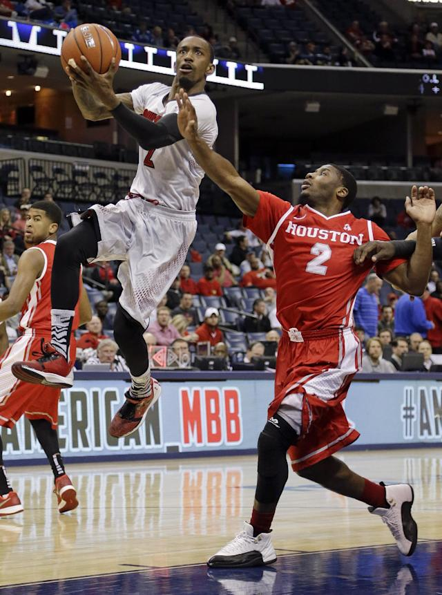 Louisville guard Russ Smith, left, lays the ball up ahead of Houston guard Brandon Morris, right, during the first half of an NCAA college basketball game in the semifinals of the American Athletic Conference men's tournament Friday, March 14, 2014, in Memphis, Tenn. (AP Photo/Mark Humphrey)