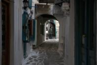 A woman wearing a face mask to help curb the spread of the coronavirus, walks at the old market in Chora, on the Aegean island of Naxos, Greece, Thursday, May 13, 2021. (AP Photo/Thanassis Stavrakis)
