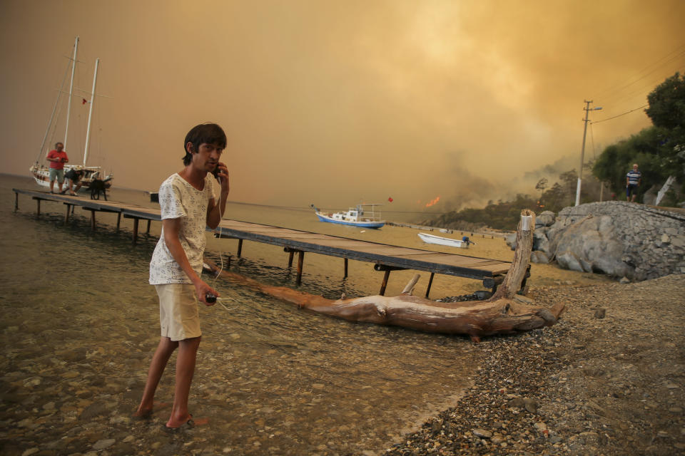 People on the beach of smoke-engulfed Mazi area as wildfires rolled down the hill toward the seashore, in Bodrum, Mugla, Turkey, Sunday, Aug. 1, 2021. More than 100 wildfires have been brought under control in Turkey, according to officials. The forestry minister tweeted that five fires are continuing in the tourist destinations of Antalya and Mugla. (AP Photo/Emre Tazegul)