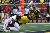 Michigan running back Hassan Haskins (25) dives into the end zone for a five-yard touchdown run against Northern Illinois in the first half of a NCAA college football game in Ann Arbor, Mich., Saturday, Sept. 18, 2021. (AP Photo/Paul Sancya)