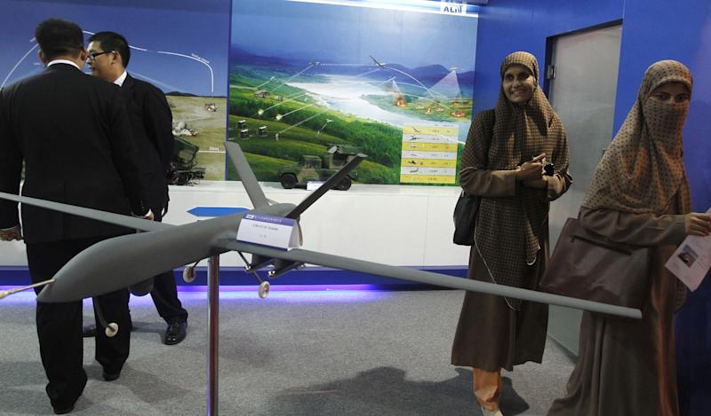 In this Thursday, Nov. 15, 2012 photo, visitors look at Pakistan-made unmanned aircraft at defense exhibition in Karachi, Pakistan. Pakistan is secretly racing to develop its own armed drones, frustrated with U.S. refusals to provide the aircraft, but is struggling in its initial tests with a lack of precision munitions and advanced targeting technology. The development of unmanned combat aircraft is especially sensitive in Pakistan because of the widespread unpopularity of U.S. drone strikes against militants in the rugged tribal region bordering Afghanistan. (AP Photo/Shakil Adil)