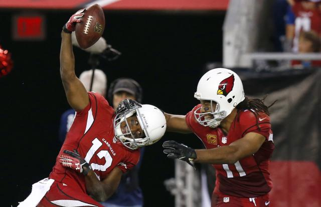 Arizona Cardinals' Andre Roberts (12) celebrates his long pass reception against the Indianapolis Colts with teammate Larry Fitzgerald, right, during the second half of an NFL football game Sunday, Nov. 24, 2013, in Glendale, Ariz. The Cardinals defeated the Colts 40-11. (AP Photo/Ross D. Franklin)