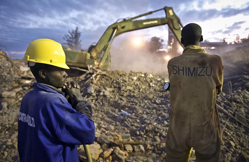 Rescue workers wait to search the rubble by hand at sunrise following the completion of rescue work by heavy machinery, at the scene of a building collapse in the eastern district of Nyagatare, Rwanda Wednesday, May 15, 2013. A four-story building under construction collapsed late Tuesday afternoon, killing at least six workers and injuring dozens more people, Rwandan police said Wednesday, though It was not immediately clear what caused the collapse or even how many people are feared buried under the rubble. (AP Photo/Mark Darrough)