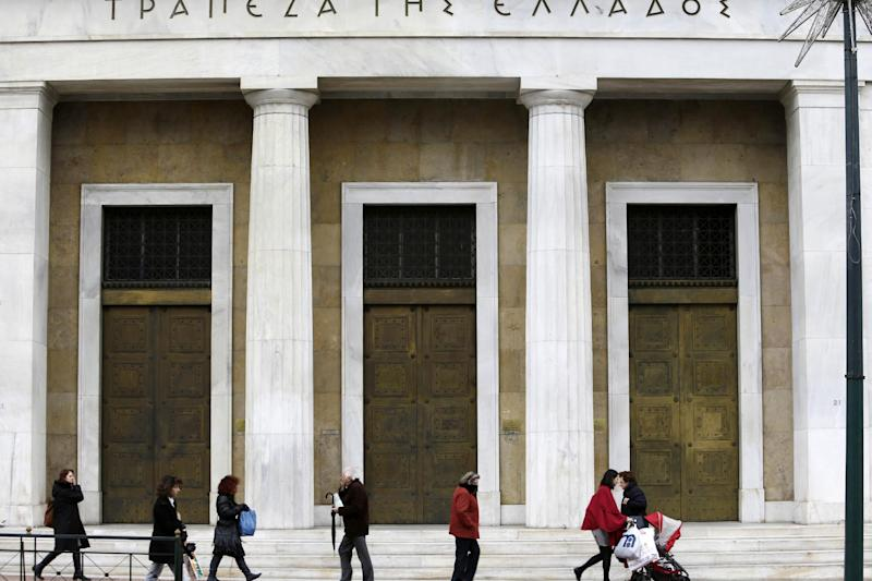 Pedestrians walk past the entrance of Bank of Greece in Athens, Tuesday, Dec. 17, 2013. Greece's central bank has joined the government in predicting that the country's economy will grow in 2014 following a savage six-year recession but cautioned about the impact of a heated political rivalry ahead of elections in May. (AP Photo/Thanassis Stavrakis)