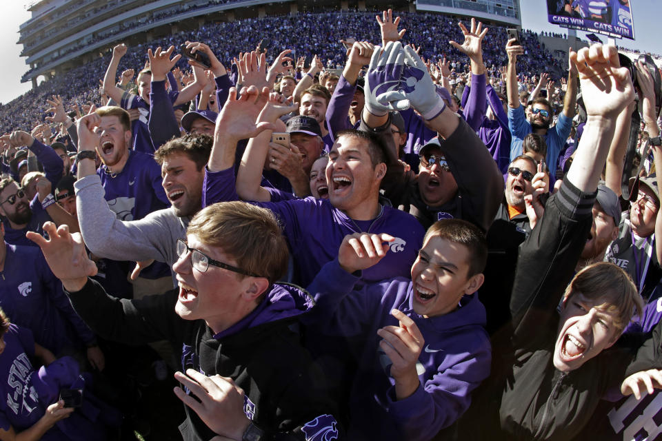 FILE - Kansas State fans cheer on the field after an NCAA college football game against Oklahoma in Manhattan, Kan., in this Saturday, Oct. 26, 2019, file photo. College football fans will head back into stadiums this weekend, and along with binoculars, sunscreen and other essentials, some will pack facemasks and proof of vaccination. With the availability of COVID-19 vaccines, the pomp and pageantry of fall Saturdays are expected to return in all their glory nearly everywhere across the country. (AP Photo/Charlie Riedel, File)
