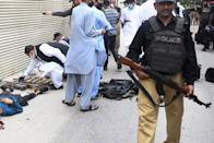 EDITORS NOTE: Graphic content / Plain cloth security personnel inspect recovered weapons next to a body of an alleged gunman outside the Pakistan Stock Exchange building in Karachi on June 29, 2020. - At least six people were killed after gunmen attacked the Pakistan Stock Exchange in Karachi on June 29, police said, with one policeman among the dead after the assailants opened fire and hurled a grenade at the trading floor. (Photo by Asif HASSAN / AFP) (Photo by ASIF HASSAN/AFP via Getty Images)