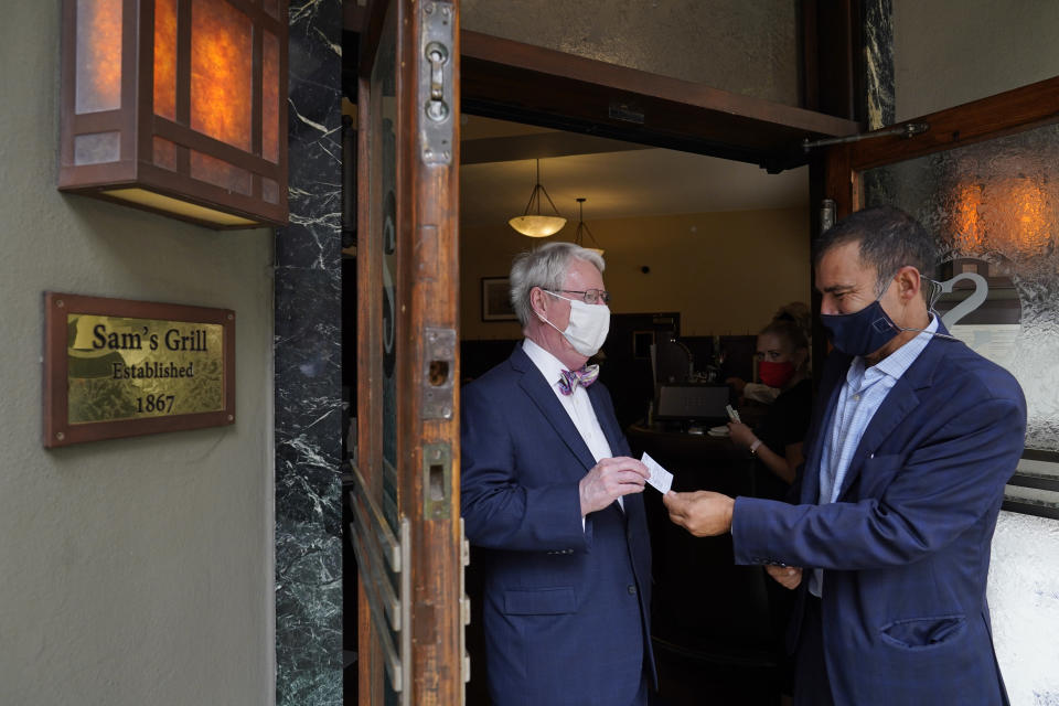 Peter Quartaroli, right, checks the vaccination card of Greg Ryken at Sam's Grill & Seafood Restaurant Friday, Aug. 20, 2021, in San Francisco. Anyone who wants to eat, drink or exercise indoors in San Francisco must show they are fully vaccinated against COVID-19 when one of the nation's most stringent restrictions on unvaccinated people takes effect Friday. (AP Photo/Eric Risberg)