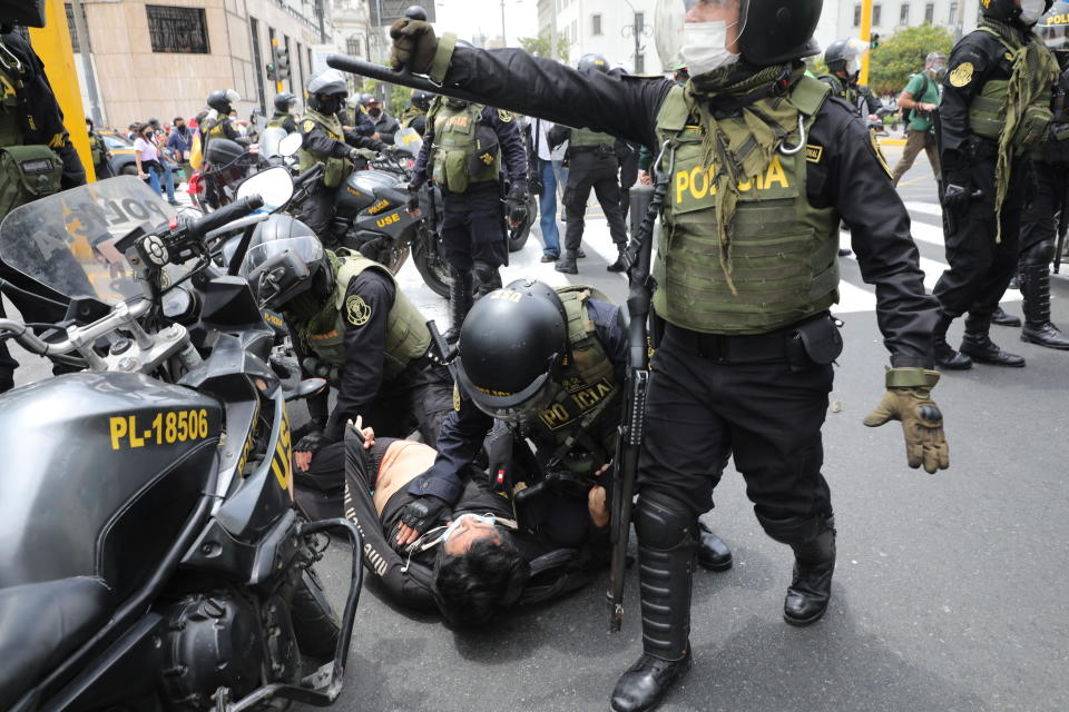 Police detain a man amid protests near Congress where lawmakers swear-in Manuel Merino, head of Peru's legislature, as the new president in Lima, Peru, Tuesday, Nov. 10, 2020. Congress voted to oust President Martin Vizcarra over his handling of the new coronavirus pandemic and unproven allegations of corruption years ago. (AP Photo/Rodrigo Abd)