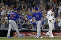 Chicago Cubs' Nico Hoerner, center, is greeted by third base coach Brian Butterfield (55) after hitting a triple as San Diego Padres third baseman Manny Machado looks on, right, during the fifth inning of a baseball game Monday, Sept. 9, 2019, in San Diego. (AP Photo/Gregory Bull)