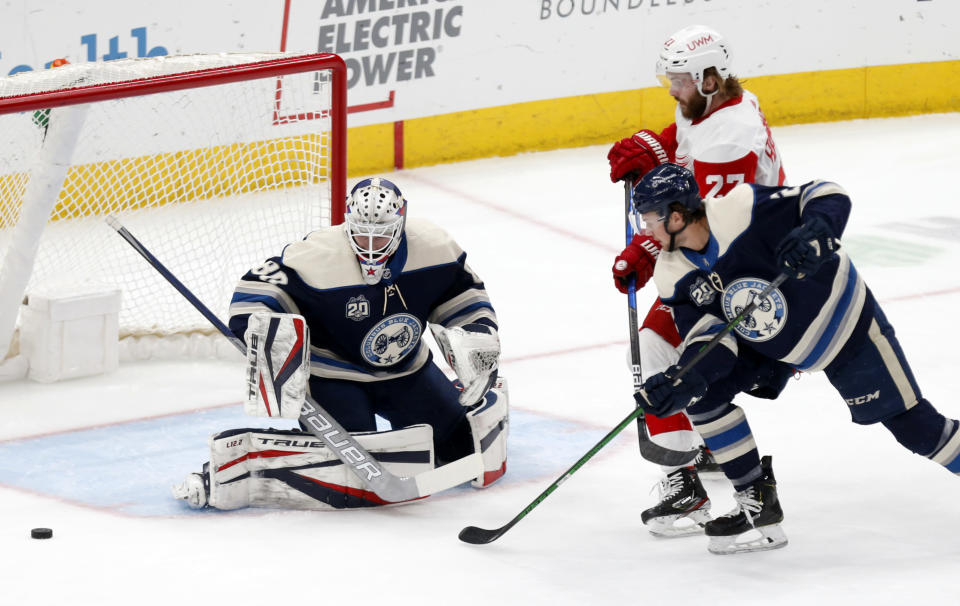 Columbus Blue Jackets goalie Elvis Merzlikins, left, stops a shot by Detroit Red Wings forward Michael Rasmussen, right, as Blue Jackets' Andrew Peeke defends during the first period of an NHL hockey game in Columbus, Ohio, Friday, May 7, 2021. (AP Photo/Paul Vernon)