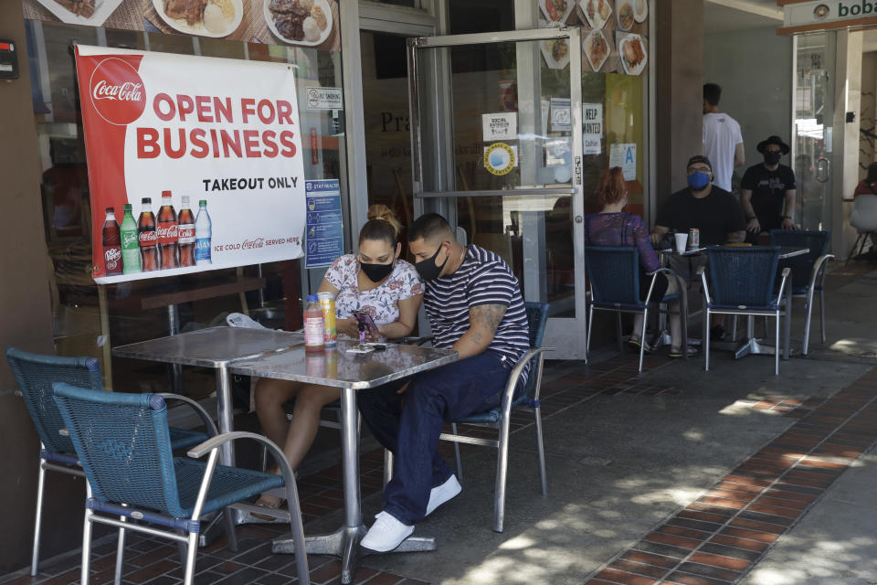 Josefina Pacheco, front left, and her husband Norberto wait to have a meal served outside of a restaurant Saturday, July 18, 2020, in Burbank, Calif. The city of Burbank has closed off some streets in the downtown district to allow restaurants to expand their outdoor seating arrangements amid the coronavirus pandemic. (AP Photo/Marcio Jose Sanchez)