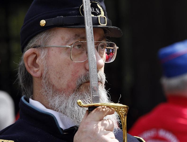 A man in a Civil War Union uniform salutes with his sword during the  military funeral for Civil War veteran Peter Knapp at Willamette National Cemetery in Portland, Ore., Friday, April 13, 2012.  Knapp is the first Civil War veteran buried at Willamette National Cemetery, Oregon's largest veterans' cemetery. His ashes had been sitting on a shelf at the Portland Crematorium since 1924.(AP Photo/Don Ryan)