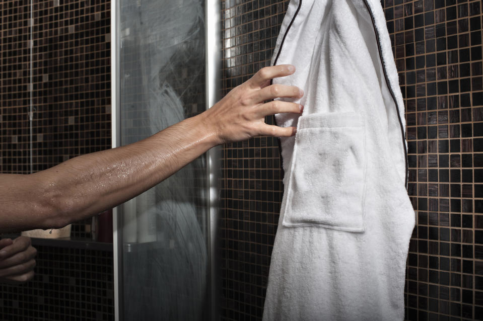 A man reaches for a bathrobe from the shower.