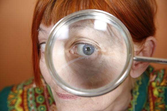 A senior woman looking through a magnifying glass.