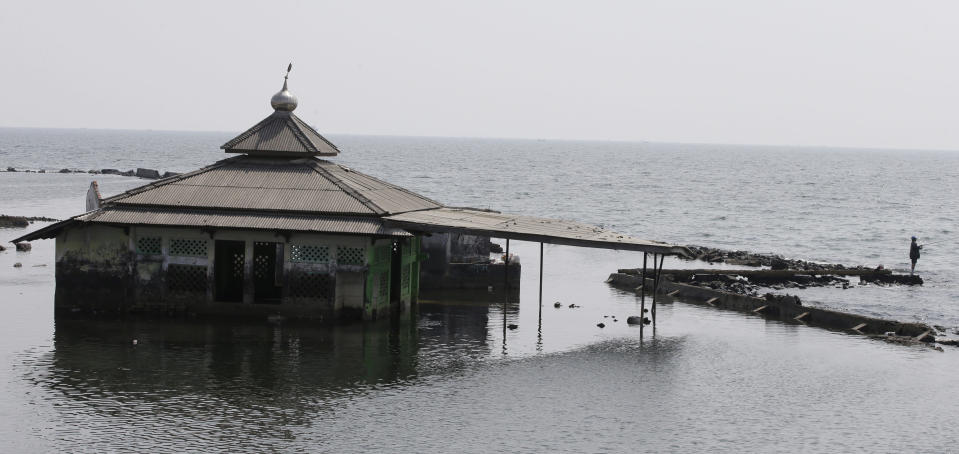 A man fishes near an abandoned mosque in Jakarta, Indonesia, Saturday, July 27, 2019. Indonesia's President Joko Widodo said in an interview that he wants to see the speedy construction of the giant sea wall to save the low-lying capital of Jakarta from sinking under the sea, giving renewed backing to a long-delayed multi-billion-dollar mega project. (AP Photo/Achmad Ibrahim)