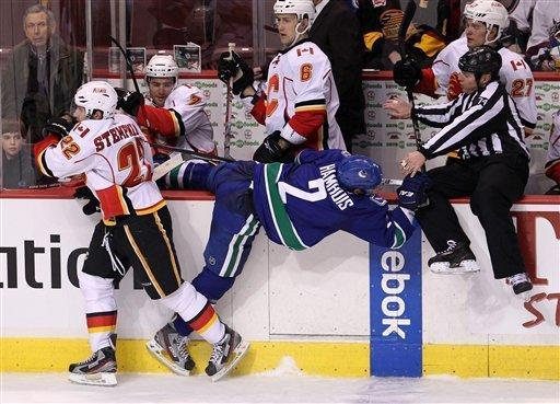 Vancouver Canucks defenseman Dan Hamhuis (2) gets put into the boards by Calgary Flames right wing Lee Stempniak (22) as linesman Lonnie Cameron (74) looks on during the third period of an NHL hockey game in Vancouver, British Columbia, Friday, Dec, 23, 2011. (AP Photo/The Canadian Press, Jonathan Hayward)