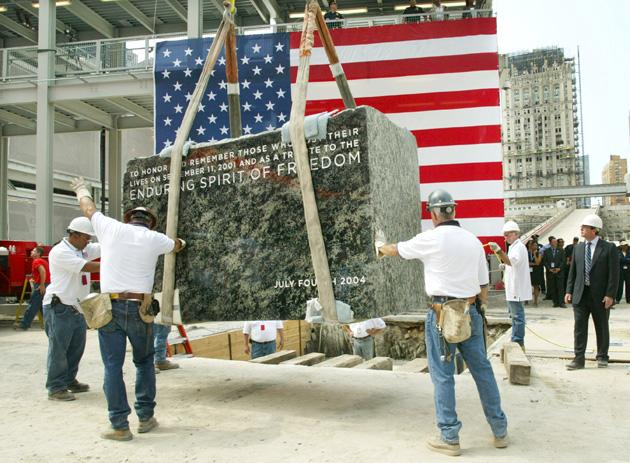 NEW YORK - JULY 4:  Construction workers move the cornerstone for the new Freedom Tower into place during the ceremony at the World Trade Center site July 4, 2004 in New York City. The new 1,776 foot tower will be the centerpiece for the World Trade Center site.  (Photo by Monika Graff/Getty Images)