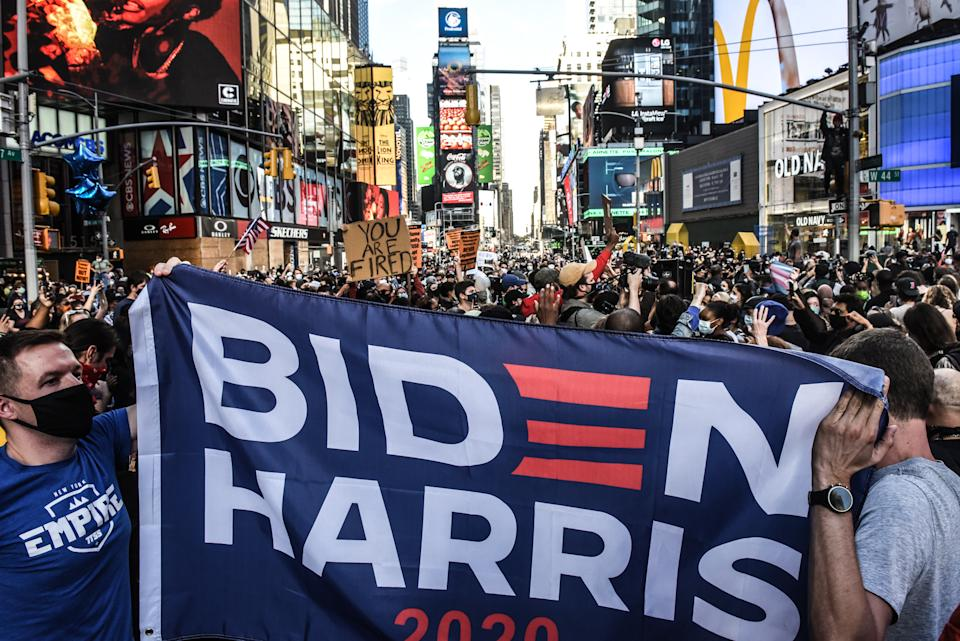 People celebrate in the streets of N.Y.C.'s Times Square after it was announced that Democratic nominee Joe Biden would be the next U.S. president. (Photo by Stephanie Keith/Getty Images)