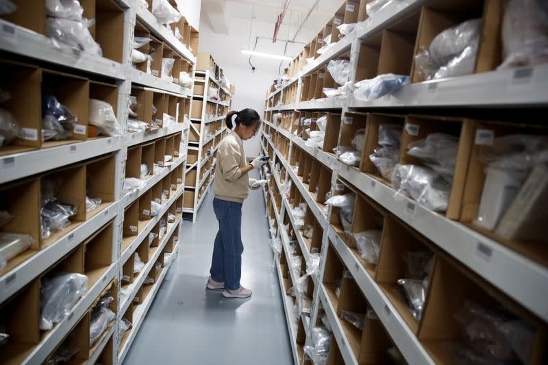 Staff member collects an order from the shelves at the warehouse of the second-hand luxury goods retail platform Plum in Beijing
