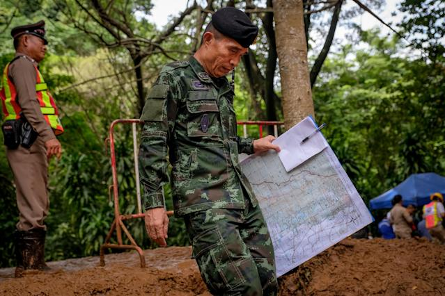 <p>An officer carring a map walks out of Tham Luang Nang Non Cave on June 30, 2018, in Chiang Rai Province, Thailand. U.S. forces and British divers joined the search for the soccer team, aged between 11 to 16, and their their 25-year-old coach. (Photo: Linh Pham/Getty Images) </p>