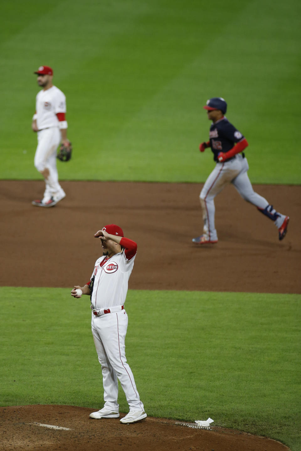Washington Nationals' Juan Soto, top right, rounds the bases after hitting a home run against Cincinnati Reds' Luis Castillo, foreground, during the sixth inning of a baseball game Thursday, Sept. 23, 2021, in Cincinnati. (AP Photo/Jay LaPrete)