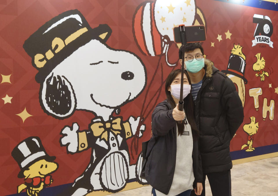 People wearing face masks to help curb the spread of the coronavirus visit the popular cartoon dog Snoopy's 70th Anniversary Exhibition in Taipei, Taiwan, Saturday, Feb, 20, 2021. (AP Photo/Chiang Ying-ying)
