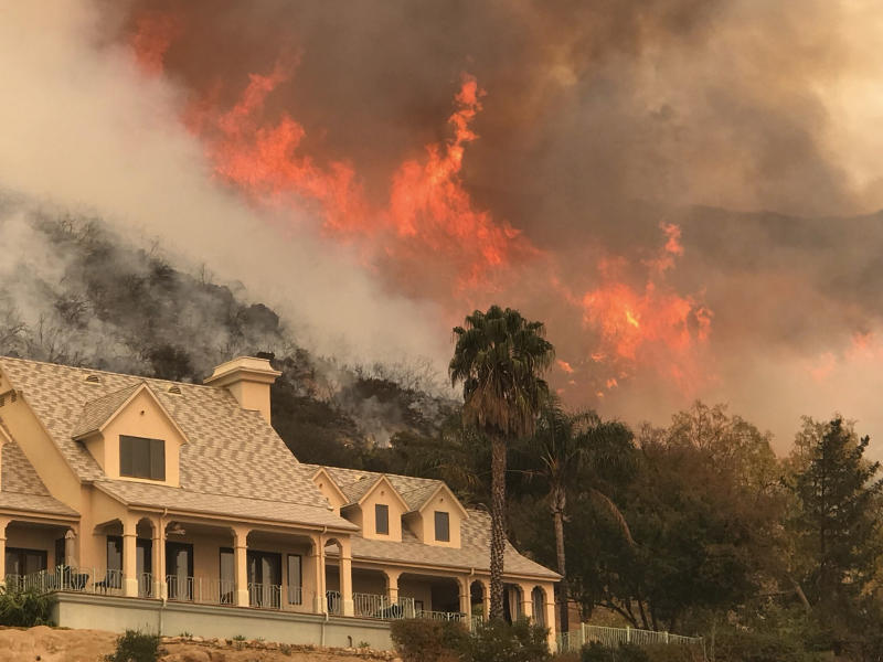 FILE - In this Thursday, Dec. 14, 2017, file photo provided by the Santa Barbara County Fire Department, shows flames from a back firing operation underway rise behind a home off Ladera Ln near Bella Vista Drive in Santa Barbara, Calif. A Southern California utility has agreed to pay $360 million to settle lawsuits brought by cities, counties and other public agencies over deadly wildfires sparked by its equipment in the last two years, including one that was later blamed for a mudslide that killed more than 20 people. An attorney for 23 public entities said Wednesday, Nov. 13, 2019, that Southern California Edison has agreed to the sum to repay taxpayers for firefighting and damage from the Thomas Fire in 2017 and Woolsey Fire last year. (Mike Eliason/Santa Barbara County Fire Department via AP,File)