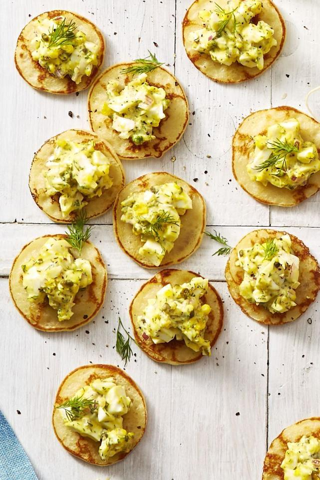 """<p>These mini pancakes give you the perfect amount of egg salad per bite, but that won't stop your guests from asking for seconds.</p><p><em><a href=""""https://www.goodhousekeeping.com/food-recipes/easy/a26767989/egg-salad-blini-bites-recipe/"""" target=""""_blank"""">Get the recipe for Egg Salad Blini Bites »</a></em></p>"""