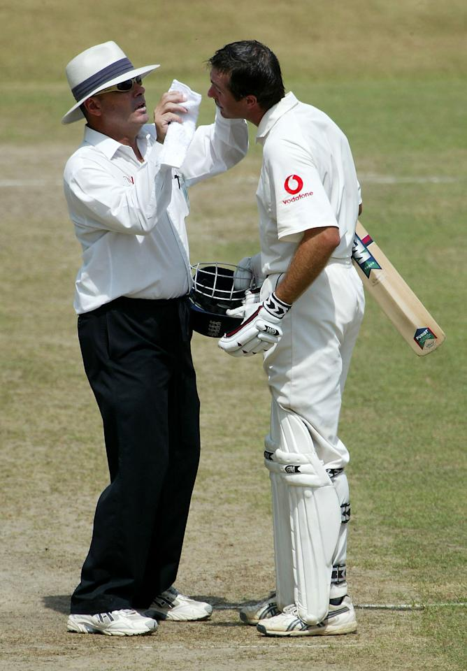 KANDY, SRI LANKA - DECEMBER 14:  England captain Michael Vaughan is assisted by umpire Daryl Harper to remove something from his eye during the fifth day of the second test between Sri Lanka and England at Asgiriya Stadium on December 14, 2003 in Kandy, Sri Lanka. (Photo by Stu Forster/Getty Images).