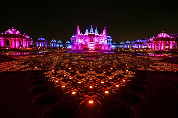 Blue, purple, and red light bathes the exterior of a large, ornate Hindu temple at night.