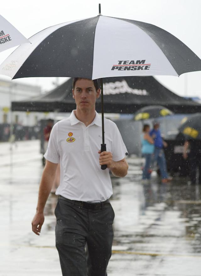 Joey Logano walks through the rain to the drivers' meeting before the NASCAR Sprint Cup series auto race at Daytona International Speedway in Daytona Beach, Fla., Saturday, July 5, 2014. (AP Photo/Phelan M. Ebenhack)