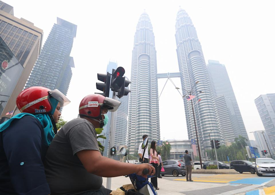 A motorist wears a mask as he travels past the Petronas Twin Towers shrouded in haze in Kuala Lumpur September 12, 2019. — Picture by Firdaus Latif