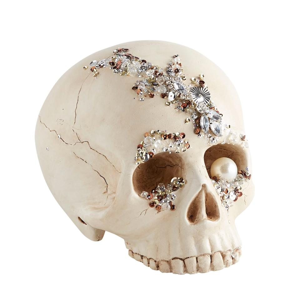 """<p>This hand-carved <a href=""""https://www.popsugar.com/buy/Bejeweled-Skull-Halloween-Decor-479976?p_name=Bejeweled%20Skull%20Halloween%20Decor&retailer=pier1.com&pid=479976&price=20&evar1=casa%3Aus&evar9=46495717&evar98=https%3A%2F%2Fwww.popsugar.com%2Fphoto-gallery%2F46495717%2Fimage%2F46495718%2FBejeweled-Skull-Halloween-Decor&list1=halloween%2Cpier%201%2Challoween%20decor&prop13=api&pdata=1"""" rel=""""nofollow"""" data-shoppable-link=""""1"""" target=""""_blank"""" class=""""ga-track"""" data-ga-category=""""Related"""" data-ga-label=""""http://www.pier1.com/bejeweled-skull-halloween-decor/4116550.html"""" data-ga-action=""""In-Line Links"""">Bejeweled Skull Halloween Decor</a> ($20) elevates your typical greige skull with a pearl in its eye socket and plenty of shiny sequins on its surface.</p>"""