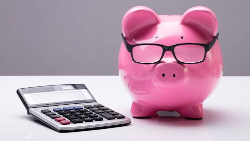 Close-up Of A Piggybank With Eyeglasses And Calculator On Desk